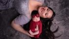 photographie de naissance fille emmaillotage rouge avec sa maman en robe grise sur fond fourrure Gémenos