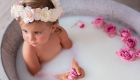 petite fille avec couronne de fleur dans le bain de lait