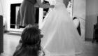 photo noir et blanc de la mariée en train de s'habiller avec une petite fille qui la regarde saint Victoret