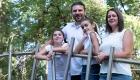 photo de famille dans un parc proche d'une rivière avec un pont métallique
