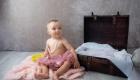 photo petit fille tient assise a coté d'une valise ancienne marignane