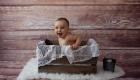 photo enfant bébé assis dans une caisse en bois avec de la dentelle sur fond bois, lugdiivne Bonomo photographe Bouches du Rhône